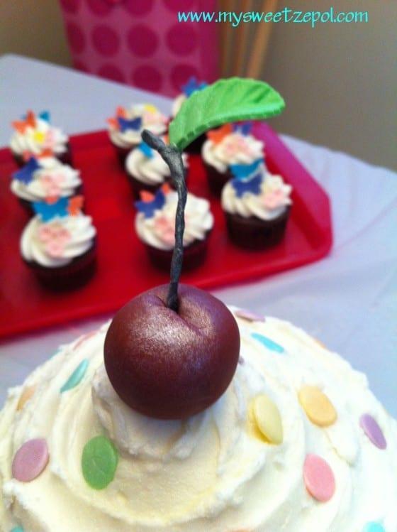 Cherry close-up on a big cupcake birthday cake