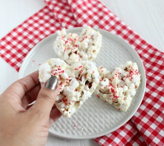 white chocolate popcorn in heart shapes with red checkers kitchen towel