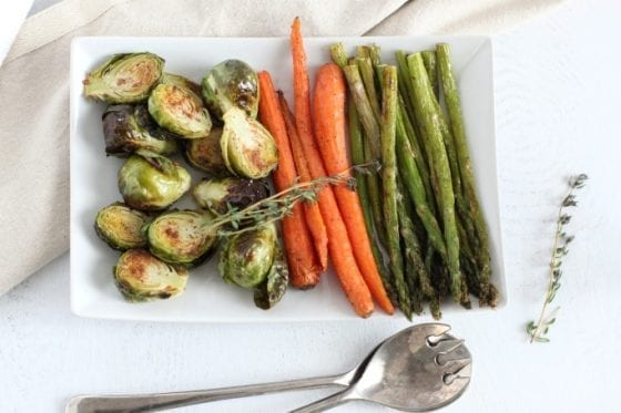 grilled carrots, grilled asparagus and grilled brussel sprouts on a plate with serving spoons