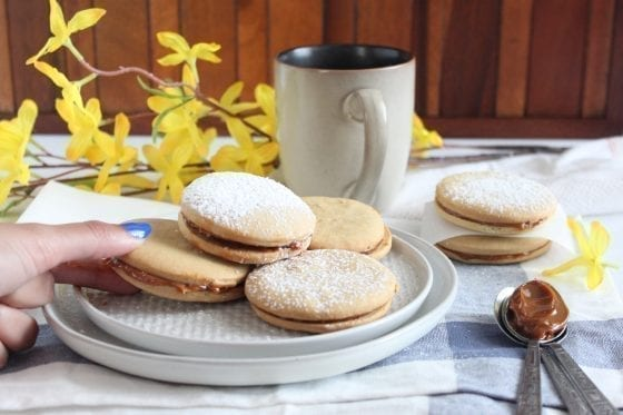 Alfajores cookies filled with dulce de leche and a cup of coffee
