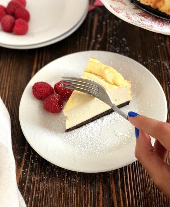 The Best Dairy Free Cheesecake with fresh raspberries and chocolate graham crust