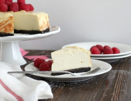 The best dairy free cheesecake on a stand, dairy cheesecake on a plate with fresh raspberries