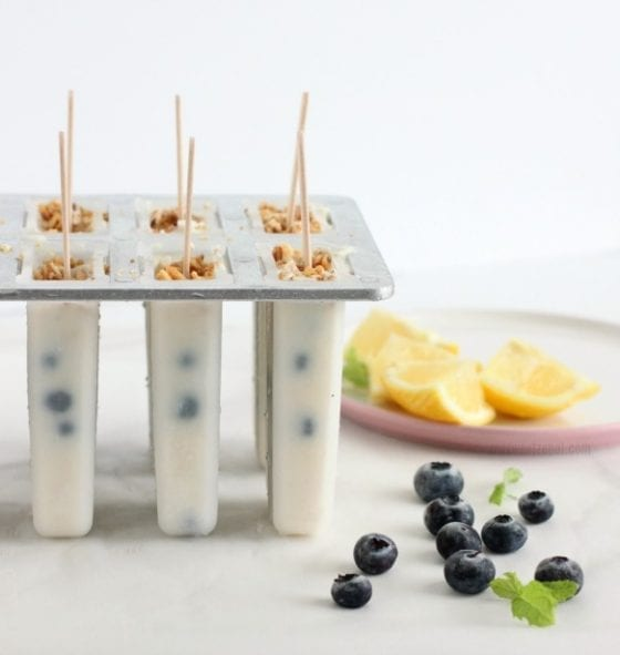 Easy Blueberry Yogurt Popsicles with granola, fresh blueberries, lemon wedges and mint leaves