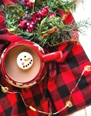 hot cocoa with a snowman marshmallow over a red flannel blanket with Christmas tree branches and Christmas lights