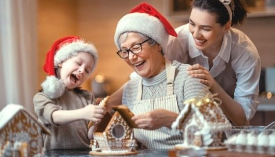 building a gingerbread house with kids, mom and grandmother for the holidays