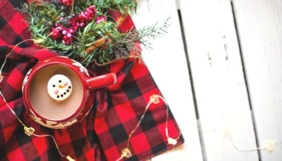 Hot cocoa with a snowman marshmallow on top of a red flannel blanket and Christmas tree branches