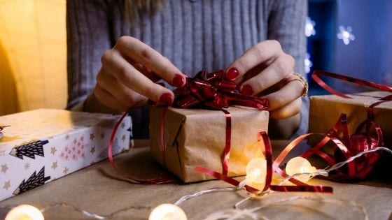 women wrapping a Christmas present with red bow