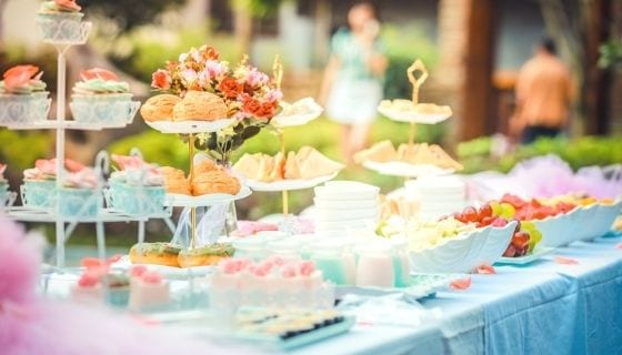 table filled with cake stands and desserts to enjoy with family and friends during Christmas day