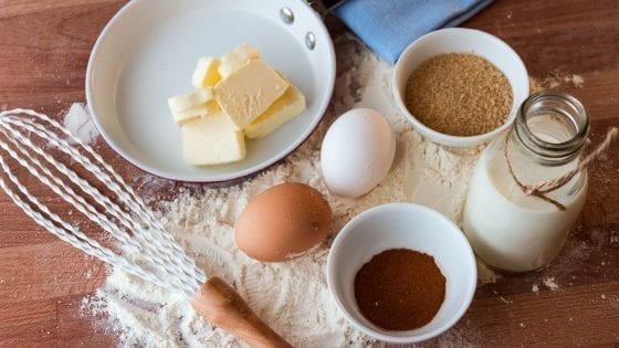 eggs, butter, sugar, cinnamon, milk and whisk-ingredients for baking