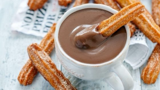 Churros with sugar and cinnamon dipped in chocolate sauce
