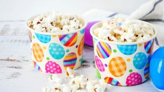 homemade popcorn with white chocolate and rainbow colors sprinkles with Easter decorated cups