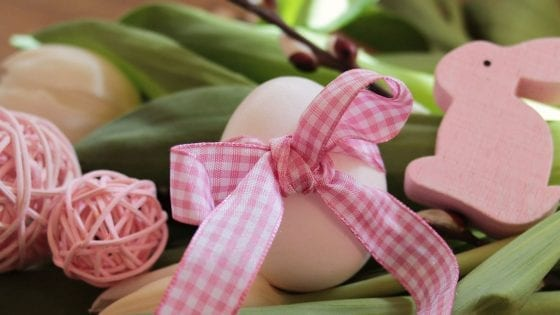 Easter egg with pink ribbon and green grass