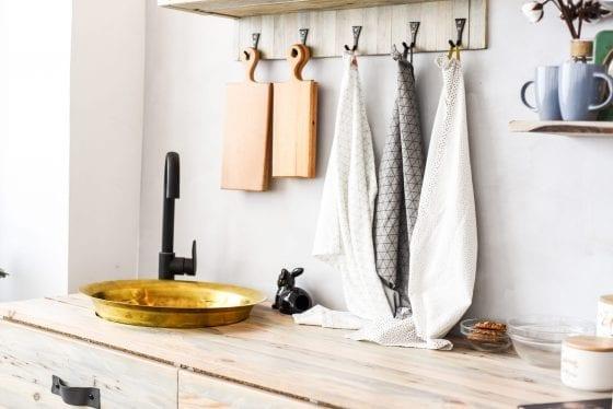 kitchen utensils, wood cutting board, kitchen towels, white kitchen