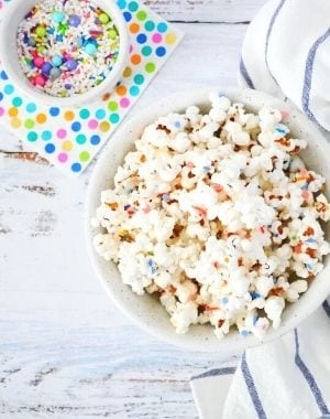homemade popcorn with white chocolate and rainbow colors sprinkles with a kitchen towel and colorful polka-dots napkin