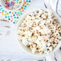 white chocolate popcorn with rainbow colors sprinkles, colorful polka-dots napking and white and blue stripes kitchen towel