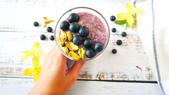Blueberry chia seed pudding, hand grabbing the serving glass, blueberries and pistachios, kitchen towel and wooden counter