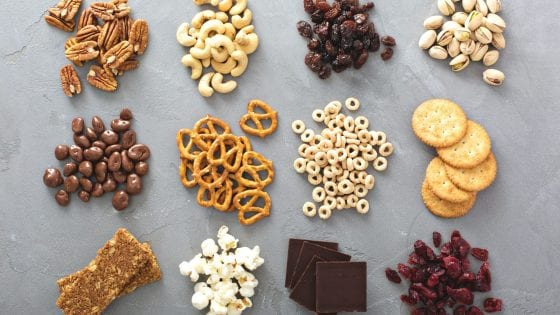 nuts, pretzels, crackers seeds, chocolate, dried fruits, popcorn, snacks on a cement slab counter