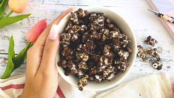 chocolate popcorn in a white bowl, hand holding the glass bowl, tulip flowers, kitchen towel, planner and pen over a wood counter