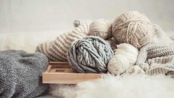 chunky knit yarn, chunky knit blanket, knitting wooden needles over a soft white blanket