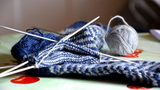 white and blue chunky knit blanket with wooden knitting needles and knitting yarn