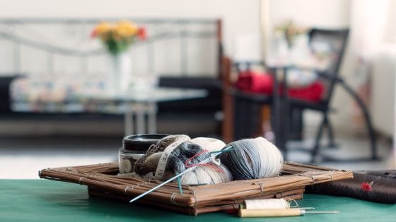 knitting yarn, knitting needles, over a wooden storage box, on a table with a room background