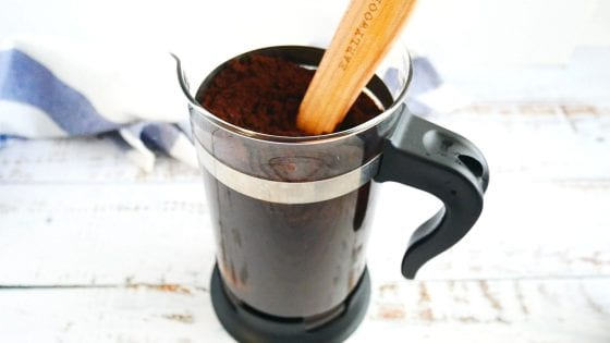 cold brew french press being mixed with an earlywood spoon