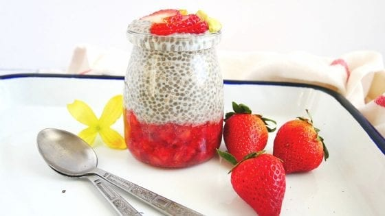 chia seed pudding with strawberry puree, fresh strawberries, pistachios, two spoons, yellow flowers, kitchen towel and enamel tray