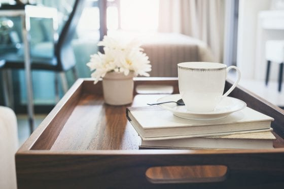 decor tray with books, cup of coffee, flower pot