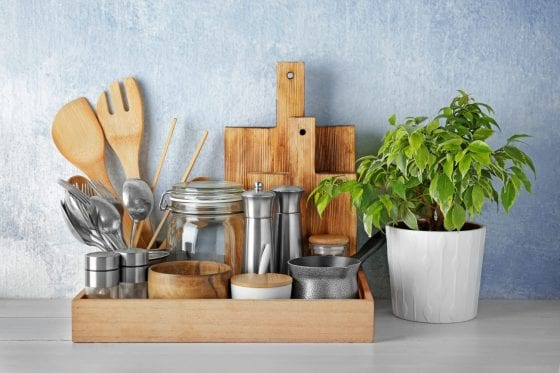 Wooden decor tray for the kitchen with kitchen utensils, tools, cutting board, wooden spoons, house plant