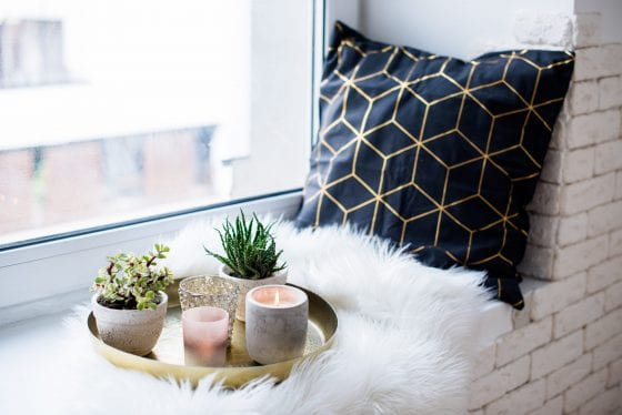 decor tray filled with candles, cactus plants and a glass drink, with a black pillow on the side over a fur blanket