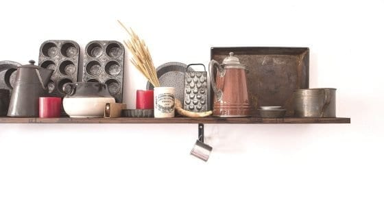 Open kitchen shelve with pot, pans, cupcake pans, muffin pans, grater, coffee pot, measuring cups, mugs, dishes, and herbs