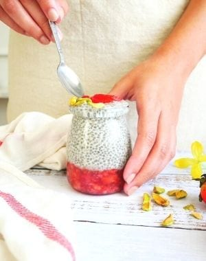 chia seed pudding with strawberry puree, hand holding a spoon, apron, kitchen towel, flowers, pistachios and fresh strawberries
