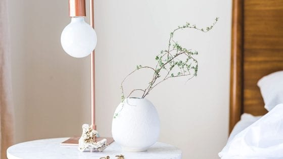 faux flowers in a white flower vase on top of a night stand. Lamp on the side. Faux foliage