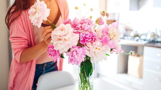 flower vase filled with pink flowers arranged by a women in a kitchen