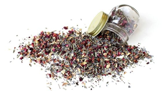 dried herbs spilling from a mason jar over the counter