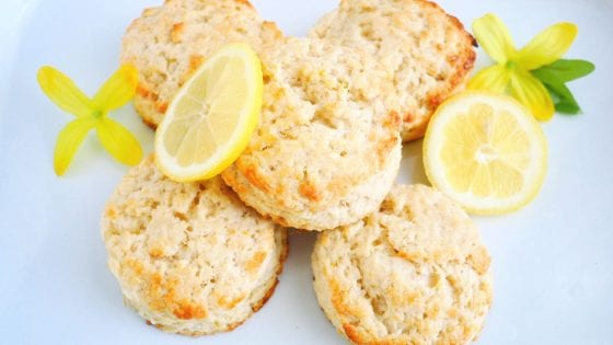 lemon biscuits with fresh lemons on top and the side, yellow flowers and a enamel tray