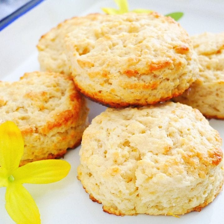 freshly baked lemon biscuits over an enamel tray, yellow flowers and fresh lemons