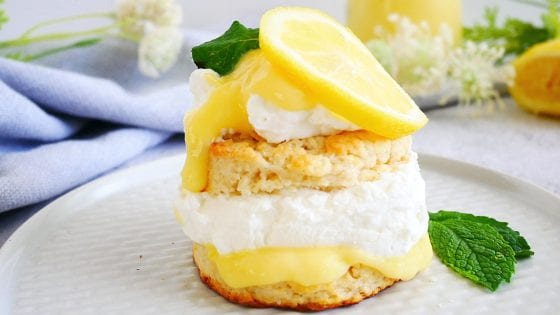 shortcake with lemon curd, whipped cream, lemon slices, fresh mint leaves, plated with kitchen towel napkin